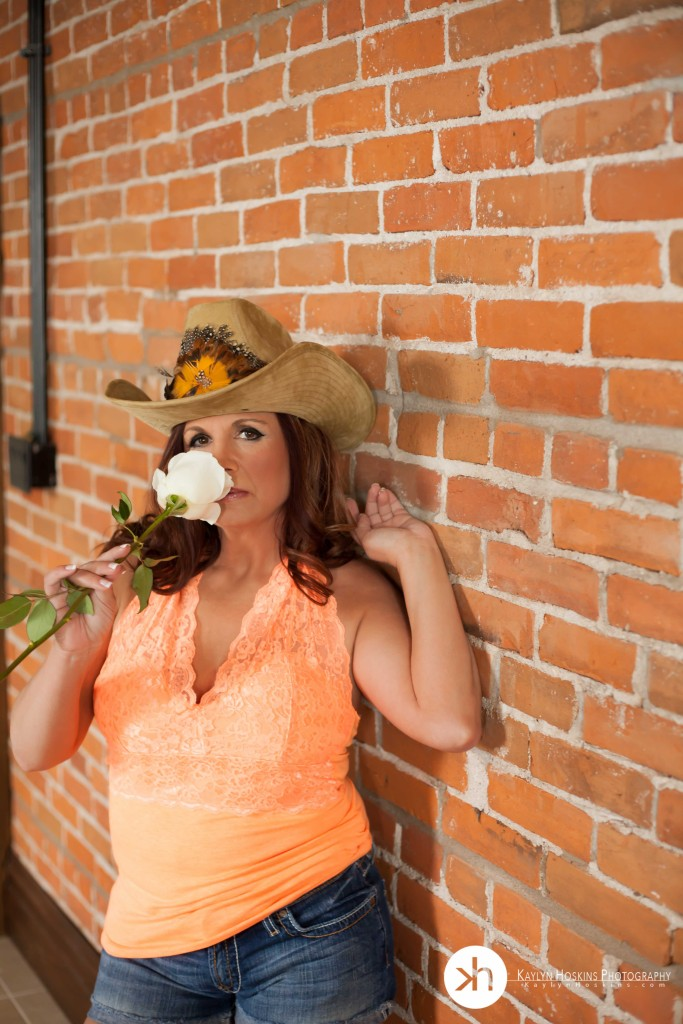 Boudoir Client Julie smells a white rose while leaning up against the brick wall at Woop Studios in Solon, IA
