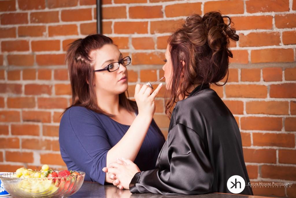 Hair & Makeup Artist Laura touches up boudoir client's lipstick during her shoot