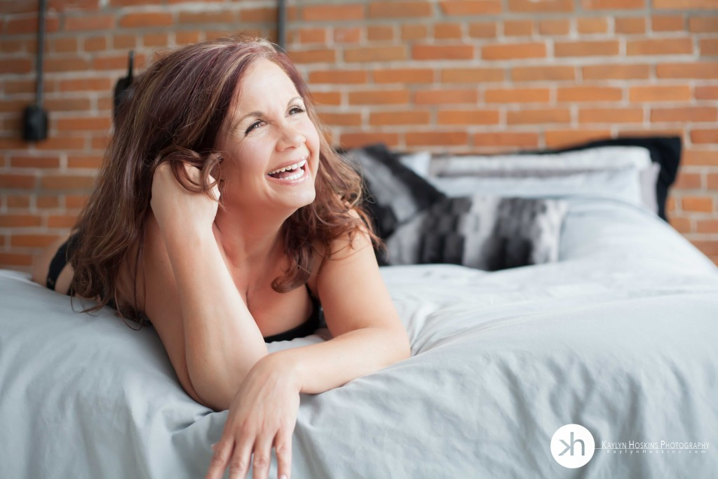 boudoir client laying on bed laughing