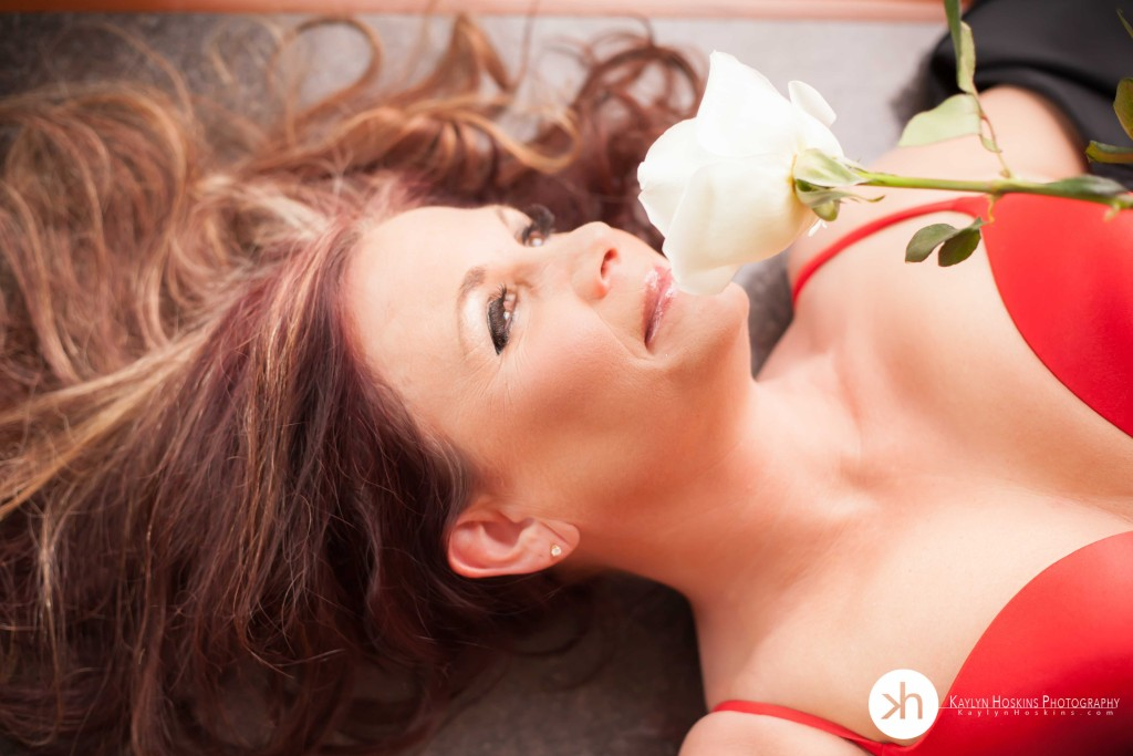 beautiful woman laying in bra smelling a white rose during her boudoir experience