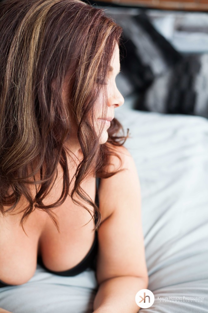 Kaylyn Hoskins Photography boudoir client lays on bed looking away