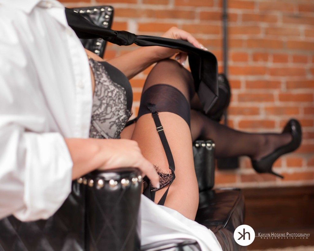 Boudoir Client Julie holds her man's tie while showing off her sexy legs