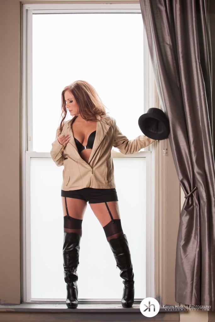 Julie stands in large window holding a hat during her boudoir experience