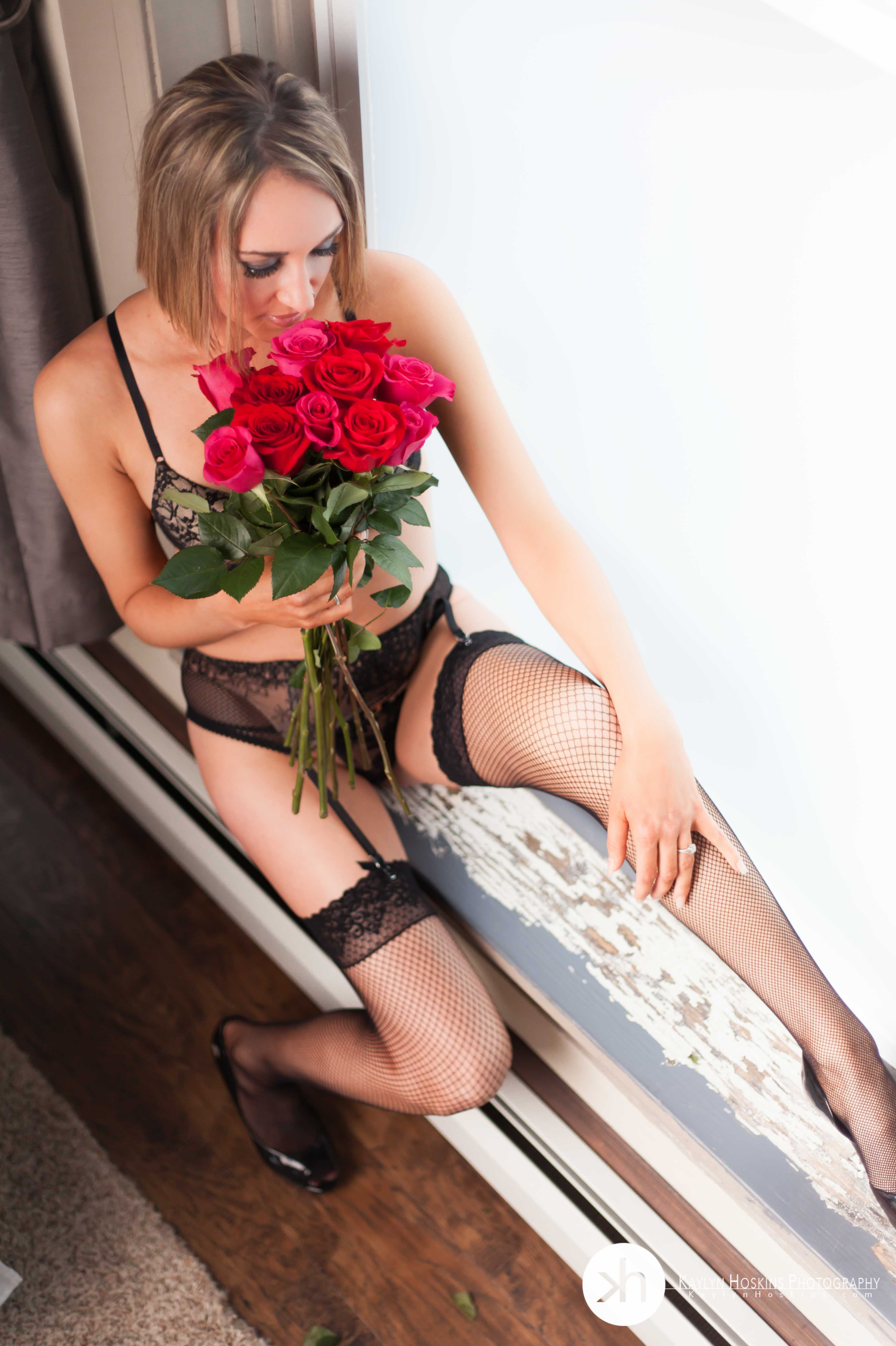 Beautiful woman sitting in window smelling dozen roses during boudoir session
