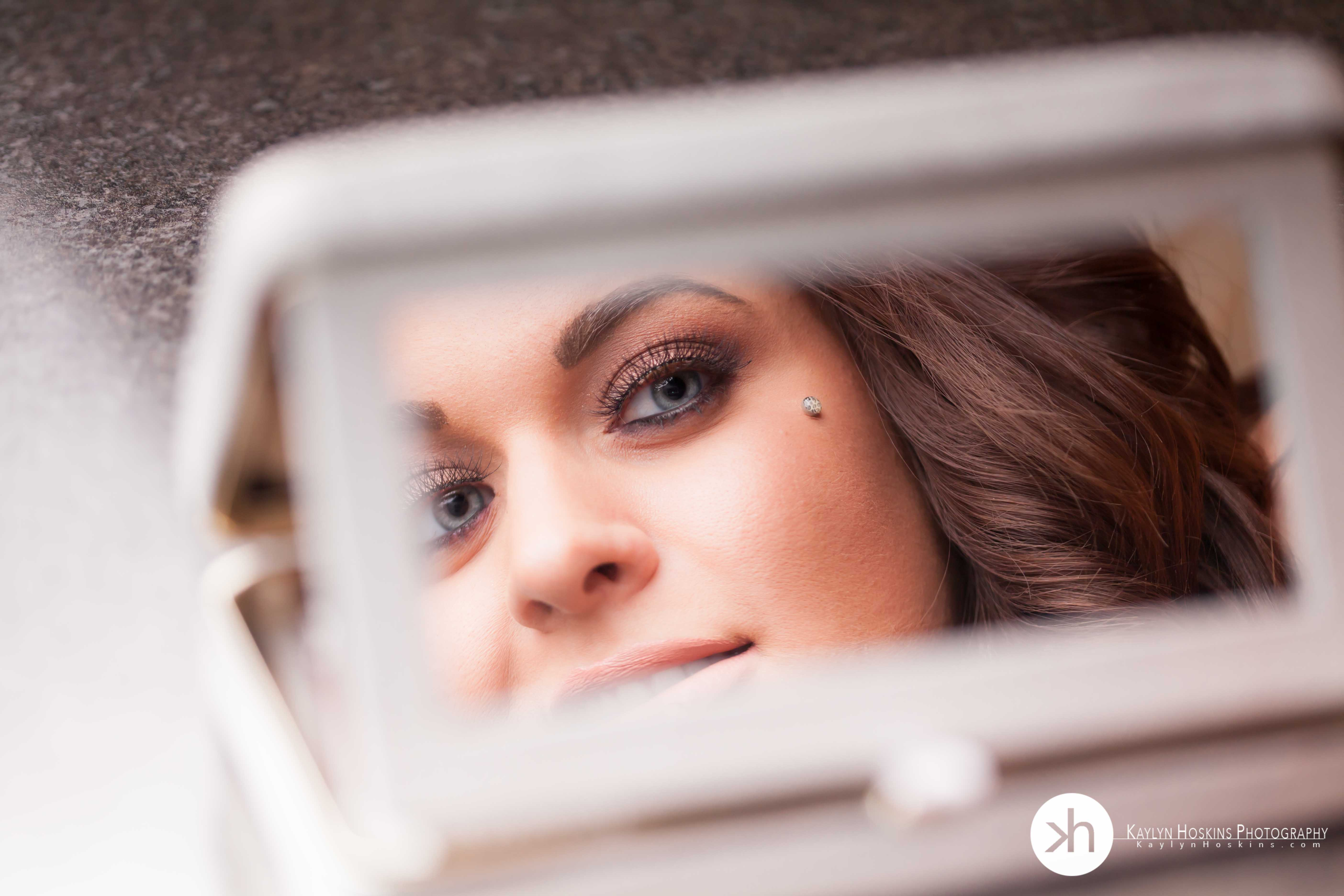 Makeup Artist looks into mirror during boudoir experience