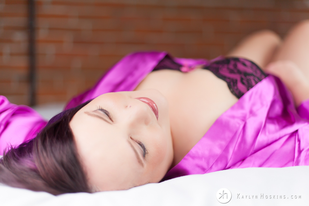 Boudoir Goddess laying on bed in lingerie during boudoir experience in Solon, Iowa