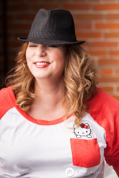 Curvy Boudoir Goddess giggles while wearing Hello Kitty tshirt while rocking sexy hat during boudoir experience