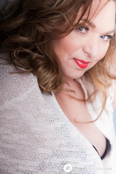 Curvy Boudoir Goddess wearing boho sweater over black bra with red lipstick during boudoir experience