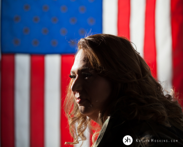 Bad Ass Boudoir Vet Goddess Genevieve looking to the left with american flag behind her