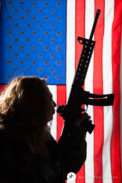 Female Military vet silhouetted holding gun with american flag background