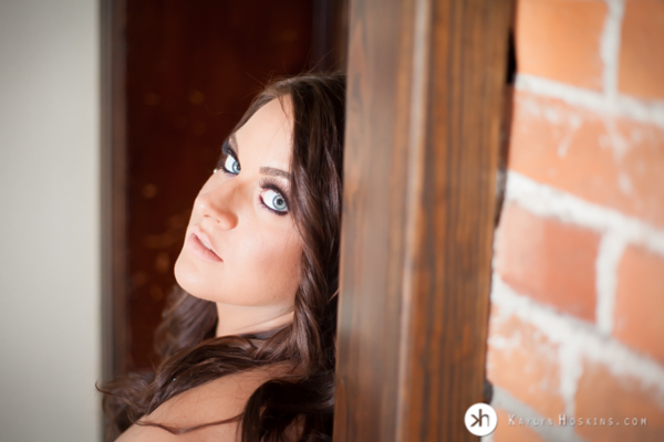 Gorgeous Boudoir Goddess sitting in doorway looking back at camera with her crazy beautiful blue eyes
