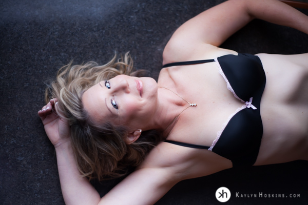 Boudoir Goddess lays on bar in lingerie during boudoir experience at Kaylyn Hoskins Photography Studio