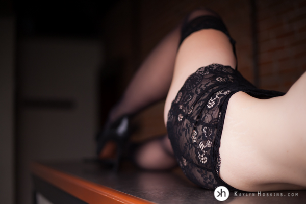 Boudoir Goddess laying on bar in black lacy garter belt during photo shoot at Kaylyn Hoskins Photography