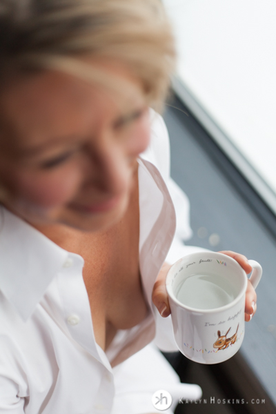 Boudoir Goddess wears husband's white shirt while holding coffee cup he gave her when they met