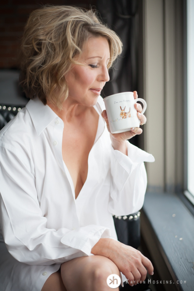 Boudoir Goddess wearing husband's dress shirt sipping out of special coffee cup during boudoir experience at Kaylyn Hoskins Photography in Solon, Iowa