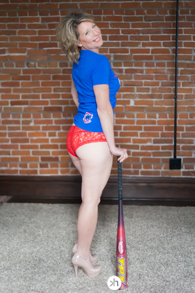 Boudoir Goddess leans on baseball bat rocking red panties with sexy Chicago Cubs t-shirt during boudoir experience in Solon, Iowa