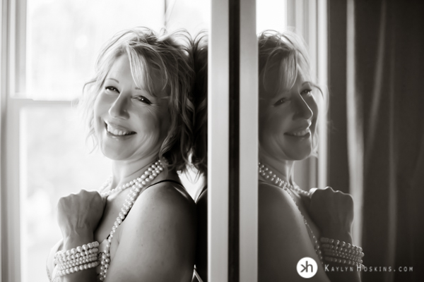Boudoir Goddess reflecting smiles at camera holding pear necklace during boudoir shoot at Kaylyn Hoskins Photography