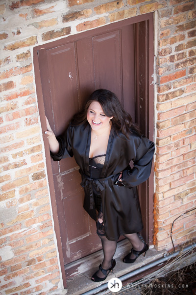 Boudoir Goddess stands outside in rad doorway wearing lingerie and silky black robe