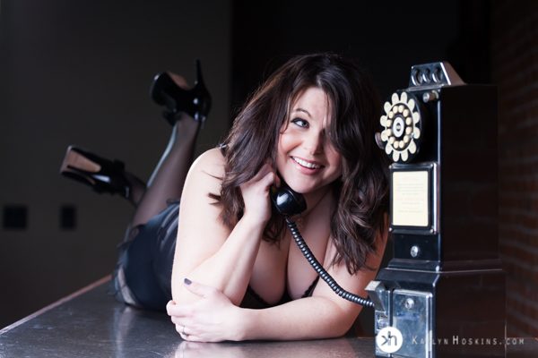 Boudoir Goddess in lingerie lays on bar talking on old vintage payphone during boudoir experience at Kaylyn Hoskins Photography
