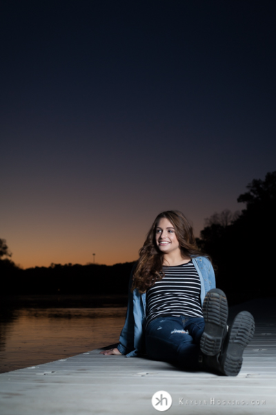 Junior Rower Aurora relaxes during sunset on the dock at P. Sue Beckwith, M.D., Boathouse during senior photo session
