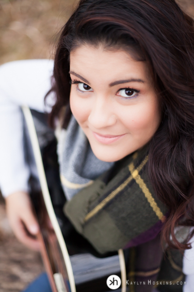 Prairie Senior looks up from playing guitar during outdoor photo session at Lake MacBride in Solon, Iowa