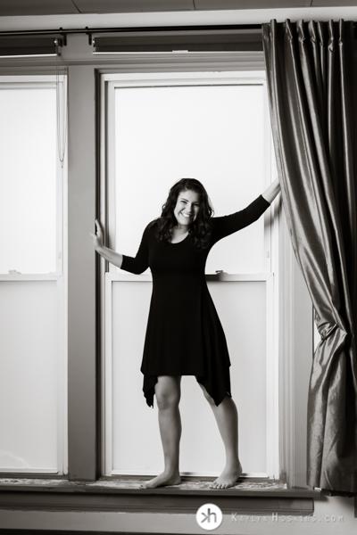 Prairie Senior wearing black dress in large window at Kaylyn Hoskins Photography studio in Solon