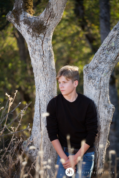 Vacaville Senior leans up against tree during senior photos