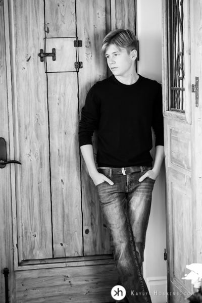California Senior Gabe leaning on wooden door during his senior portraits with Kaylyn Hoskins Photography