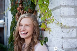 Gorgeous high school senior leaning up against brick wall laughing during senior photo session in Iowa City