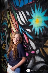 High School Senior smiling, while leaning on rad graffiti wall downtown iowa city behind studio 13