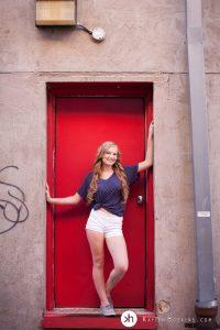 Solon Senior standing in red doorway behind University Camera downtown Iowa City