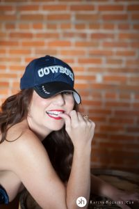 Boudoir Goddess wears her man's Cowboys hat while playfully nibbling her thumb