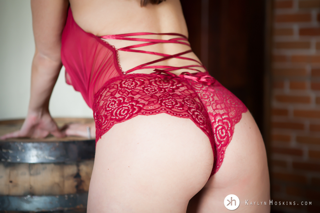 Boudoir goddess in red one piece lingerie leans on whiskey barrel to show her booty