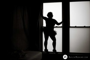 Curvy Woman silhouetted in large window wearing stilettos and tutu