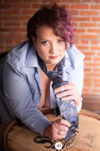 Curvy Girl leaning on whiskey barrel in man's shirt and tie