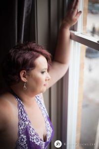 Gorgeous Curvy girl in purple lingerie looking out big front window during boudoir shoot