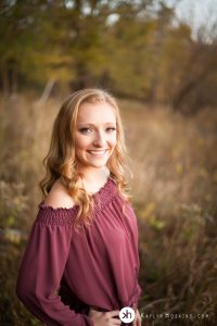 Beautiful senior smiles while standing in brush out at lake macbride in solon, iowa