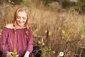 Solon Senior playfully looks down at weeds during her fall senior session