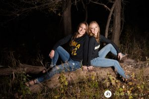 Solon Senior and her big sister pose on log at lake macbride during fall senior session