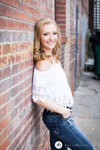 Solon Senior Leaning on brick wall downtown Iowa City during Senior Photo Session