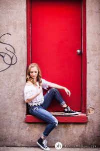 Solon Senior Olivia sitting in red backdoor of University Camera downtown Iowa City