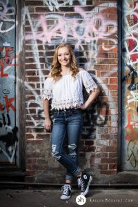 Solon Senior standing in front of Graffiti wall in Alley downtown Iowa City