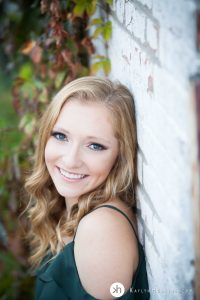 Solon Senior Liv leans up against white brick wall in downtown Iowa City Alley
