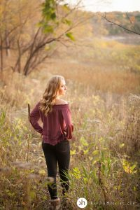 Iowa Senior girl standing by lake macbride during fall senior photos