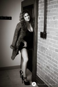 boudoir goddess standing in doorway in fur coat and black stilettos during boudoir shoot