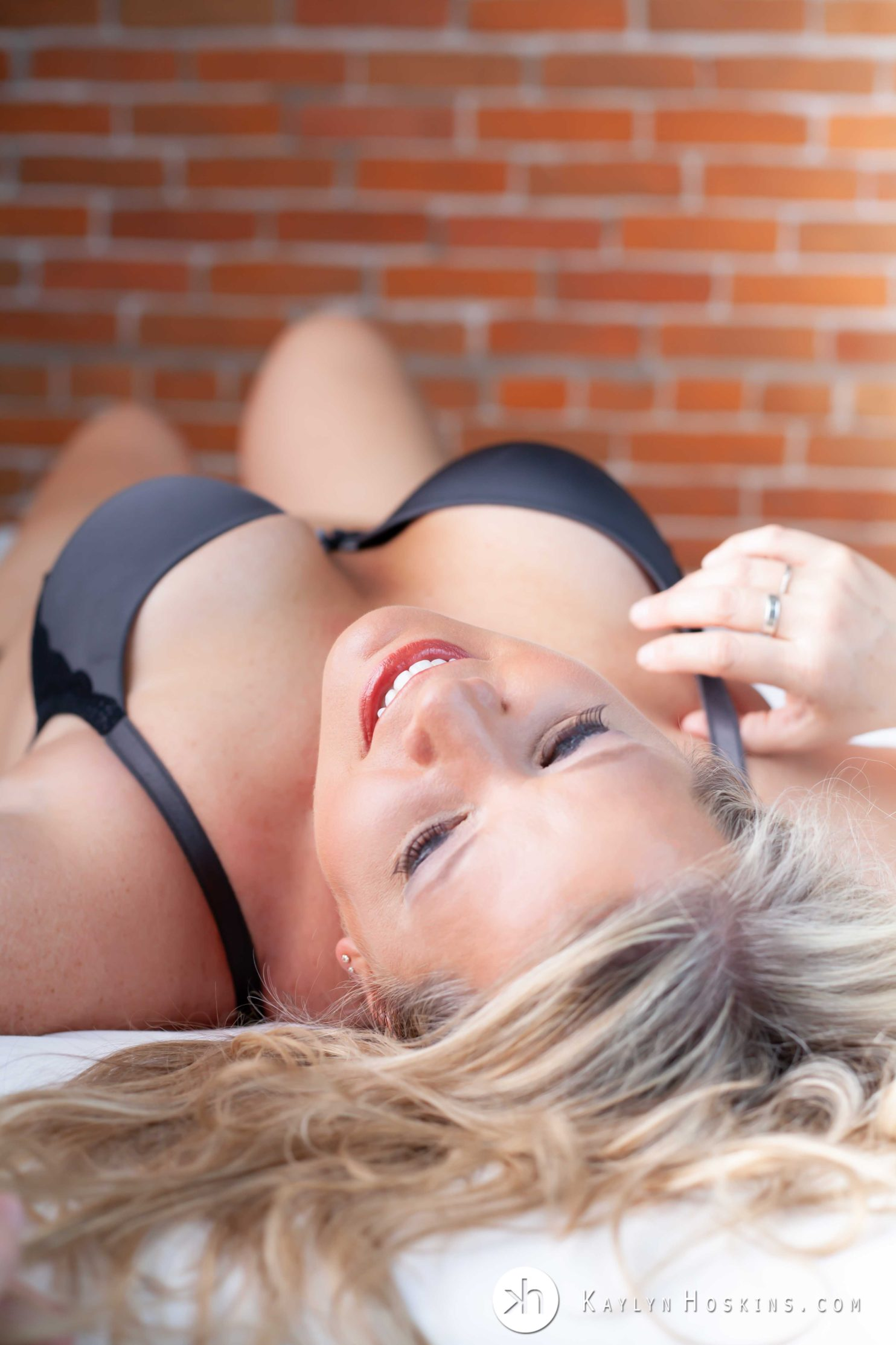 Gorgeous nurse sexily lays face up on bed in bra and panties during boudoir shoot in Solon, Iowa