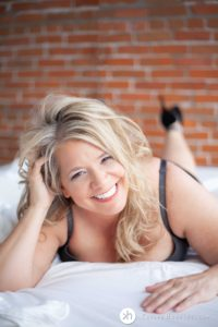 Gorgeous boudoir goddess smiles big at the camera while laying on bed in lingerie during boudoir photo shoot