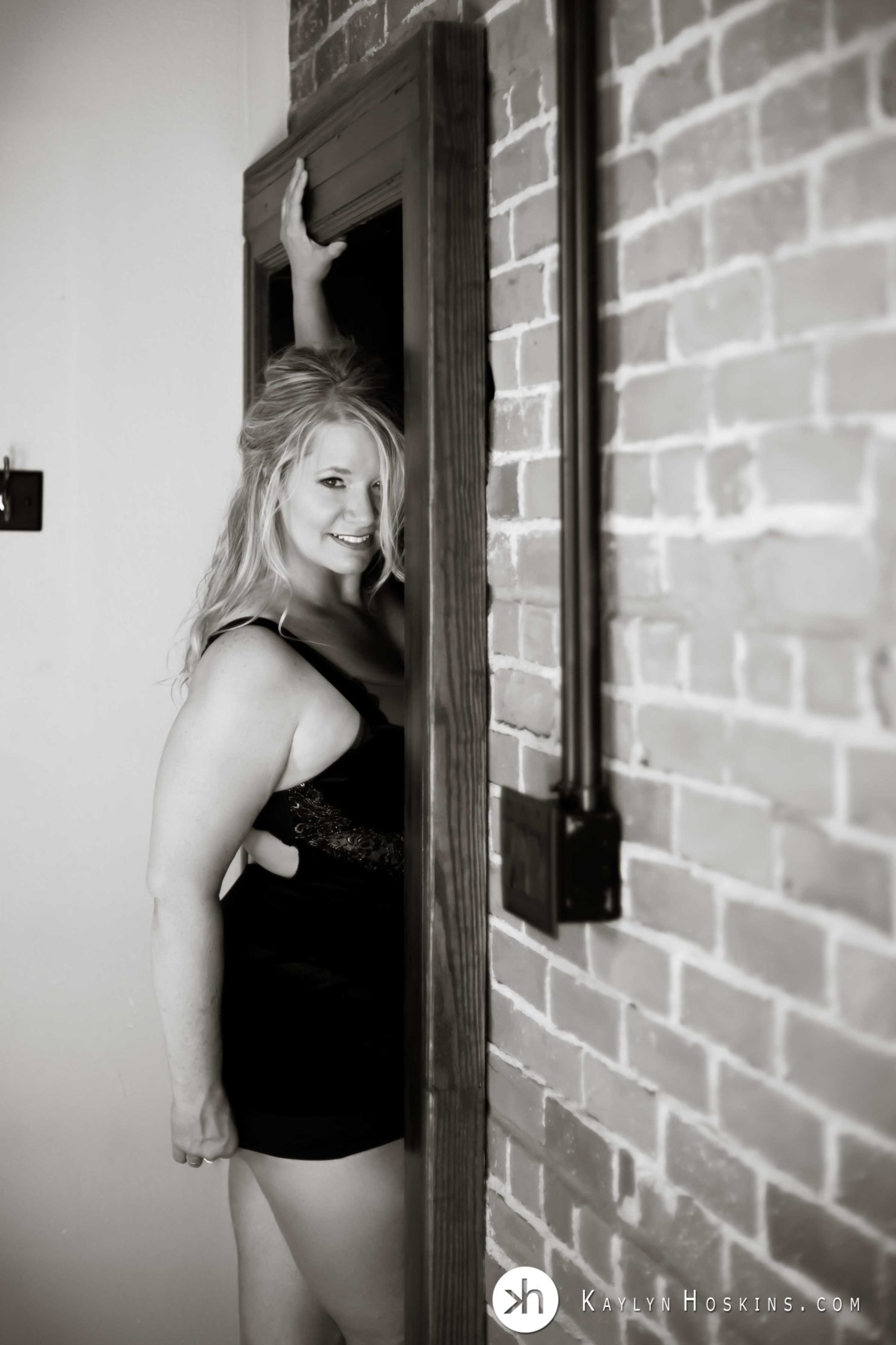 Gorgeous Blonde standing in old wooden doorway wearing black lingerie during boudoir photo shoot