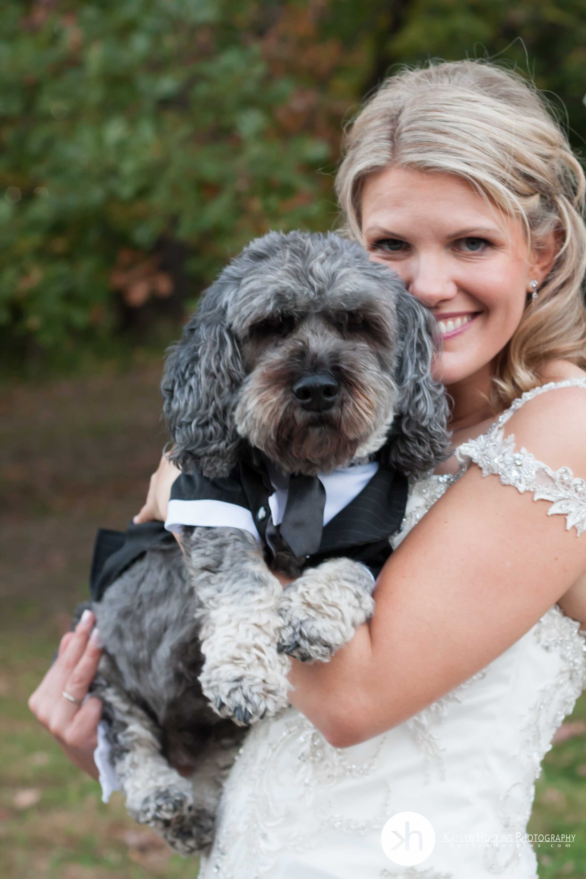 Bride wearing wedding dress holds her dressed up dog during wedding photos in Iowa