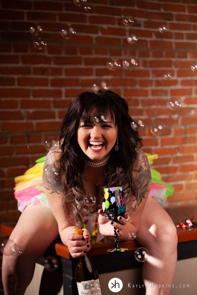boudoir goddess laughing sitting on bar in rainbow tutu holding Happy Birthday wine glass with bubbles floating about